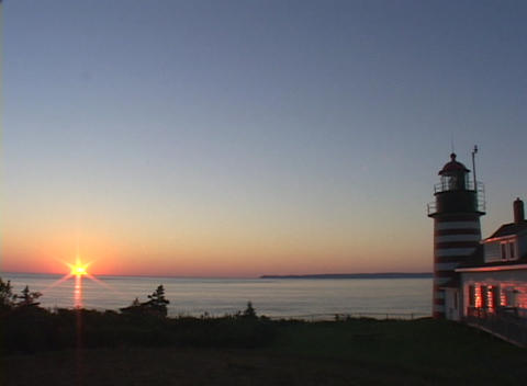The West Quoddy Head Lighthouse adorns the coastline at golden-hour Footage
