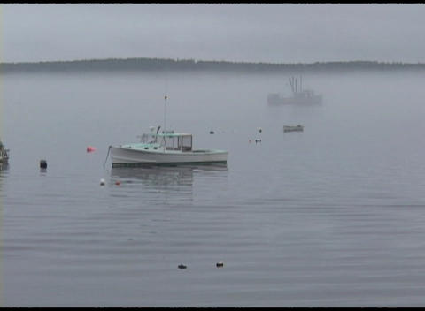 Long-shot of two fishing boats moored offshore along the Main or New England coast in the fog Footage