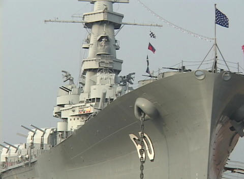 A battleship sits in the harbor with flags flying Stock Video Footage
