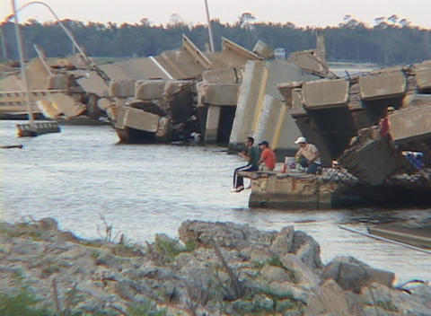 Men fish along a destroyed causeway on the Gulf Coast of... Stock Video Footage
