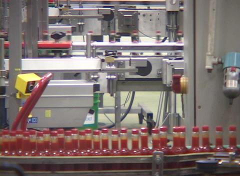 Bottles run along an assembly line at a hot sauce factory... Stock Video Footage