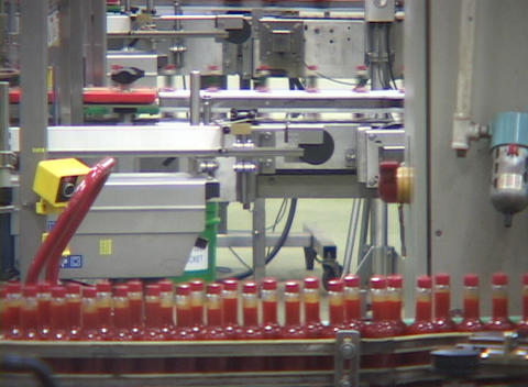 Bottles run along an assembly line at a hot sauce factory... Stock Video Footage