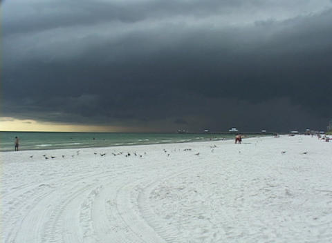 Vacationers walk on a beach under a cloudy sky Stock Video Footage