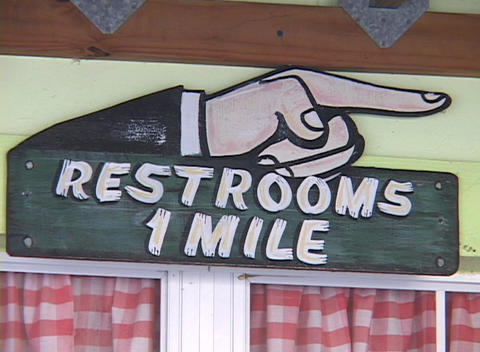 "A sign reads Restrooms 1 Mile""."" Stock Video Footage"