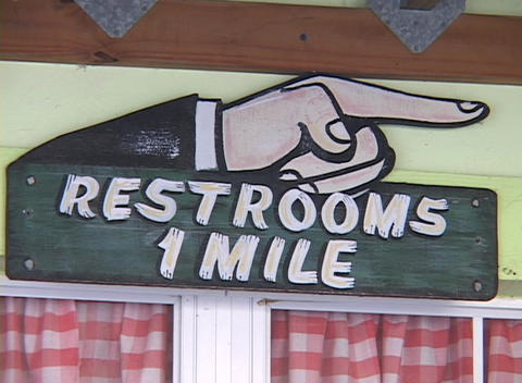 "A sign reads Restrooms 1 Mile""."" Footage"