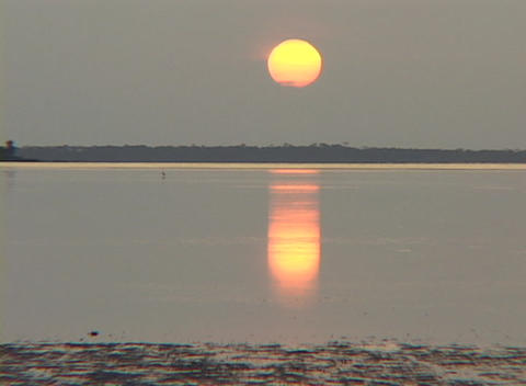 The sun reflects off smooth water during golden hour Stock Video Footage