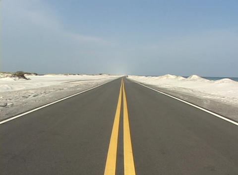 Sand sits on the side of a deserted highway Stock Video Footage