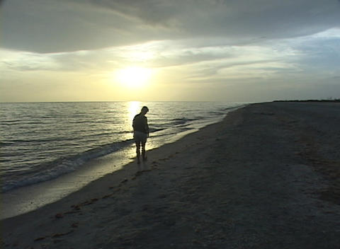 A woman walks along the beach as the waves roll in Stock Video Footage