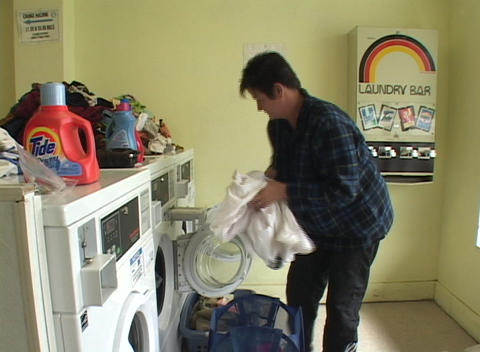 A woman does a load of laundry in a Laundromat Stock Video Footage