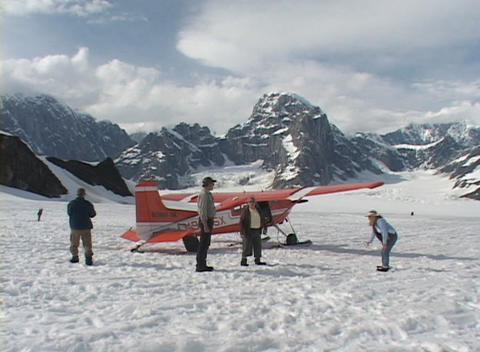 Tourists mill around a ski plane after it has landed on a glacier Footage
