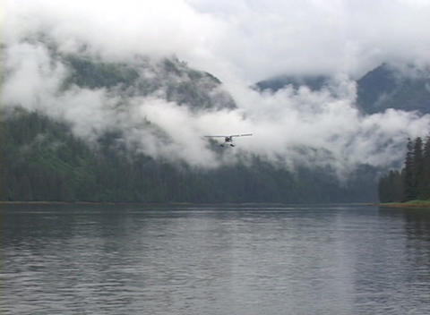 A float plane flies past in a gorgeous Alaskan fjord Stock Video Footage