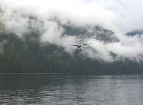 A float plane flies past in a gorgeous Alaskan fjord Footage