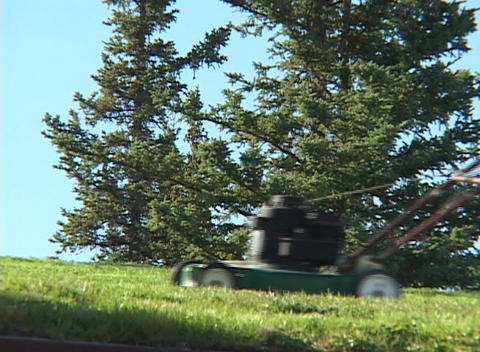 A man uses a lawnmower to mow grass Stock Video Footage