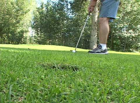 A golfer putts the ball into the cup Stock Video Footage