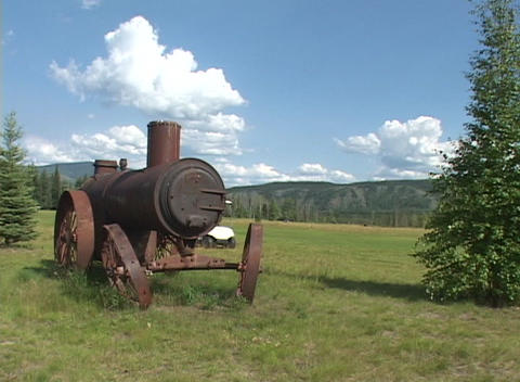 An abandoned steam engine near a golf course as a golf cart passes Footage