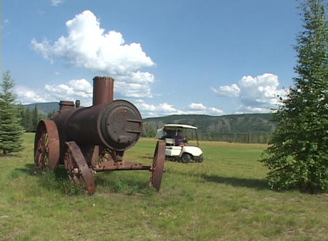 An abandoned steam engine near a golf course as a golf... Stock Video Footage