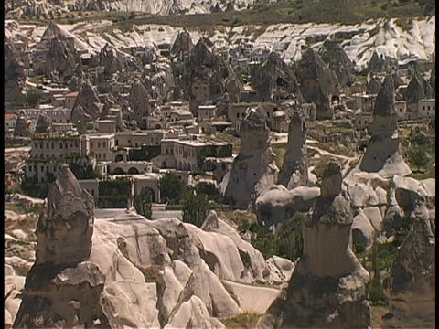 Fairy-chimney rock formations rise above the desert in... Stock Video Footage