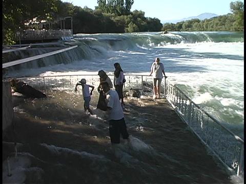 Tourist splash through a flooded observation deck at a dam in Turkey Footage