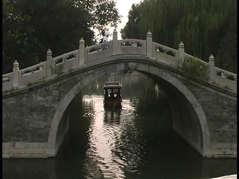A boat floats under the Moon Bridge in China Stock Video Footage