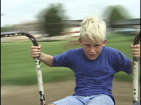 A young boy spins on a merry-go-round Stock Video Footage