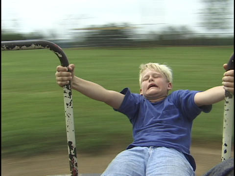 A young boy spins on a merry-go-round Footage