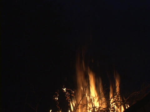 A burning campfire sends sparks into the dark sky Footage