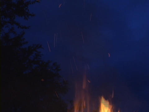 A burning campfire sends sparks into the dark sky Stock Video Footage
