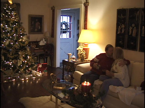 A middle aged couple sits on a couch at Christmas time Footage