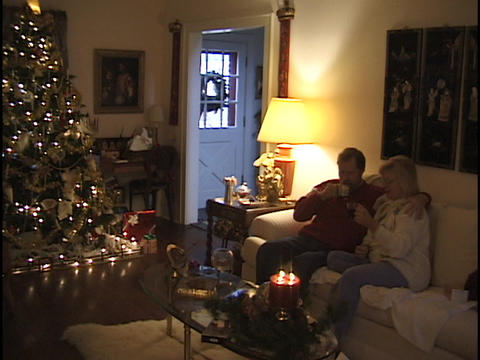 A middle aged couple sits on a couch at Christmas time Stock Video Footage