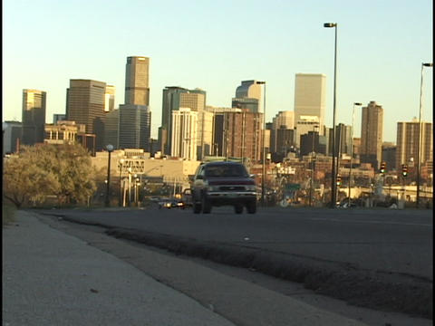 Traffic passes by on a highway leaving the Denver, Colorado skyline in the background Footage