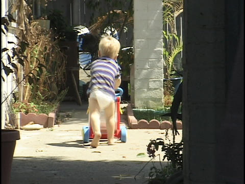 A toddler pushes a walk-behind toy Stock Video Footage