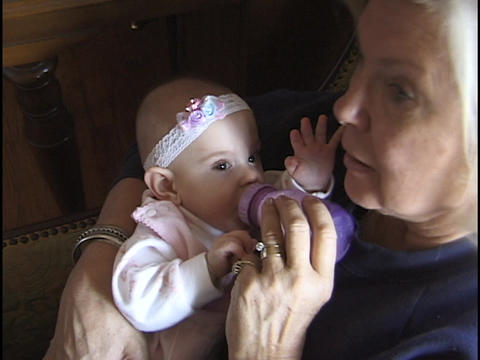 A grandmother feeds a bottle to a baby girl Stock Video Footage