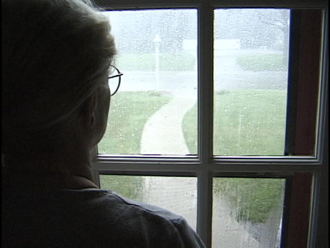 A women watches the rain outside the window Stock Video Footage