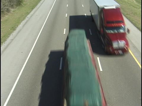 Semi trucks pass directly underneath on an interstate... Stock Video Footage