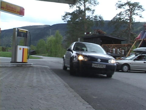 A small economy car drives into a gas station in Europe Footage