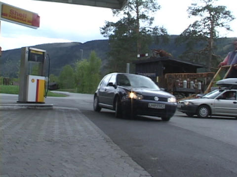 A small economy car drives into a gas station in Europe Stock Video Footage