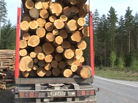 A logging truck pulls away from a log pile on the side of... Stock Video Footage