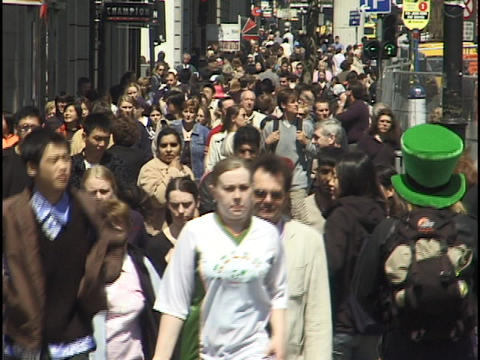 A large crowd of people walk down a busy city sidewalk Footage