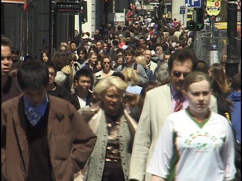 A large crowd of people walk down a busy city sidewalk Stock Video Footage
