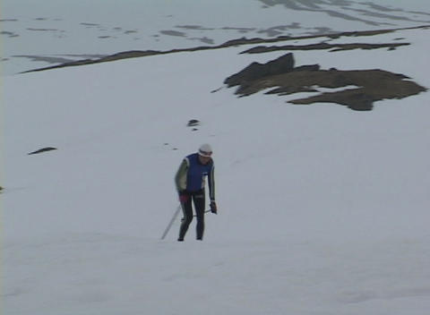 Following-shot of a cross country skier striding up a snowy hillside Footage