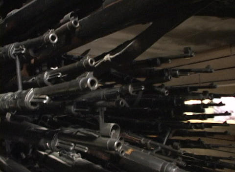 Pan-up shot of racks of weapons in a munitions depot Stock Video Footage