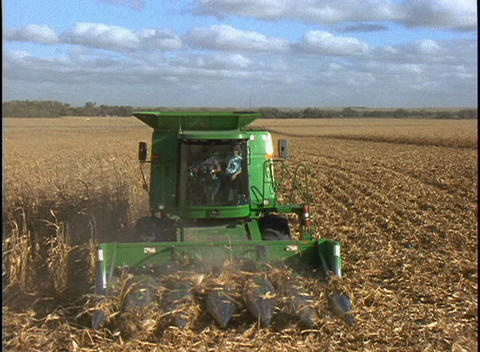 A farmer drives a combine machine through several rows of... Stock Video Footage