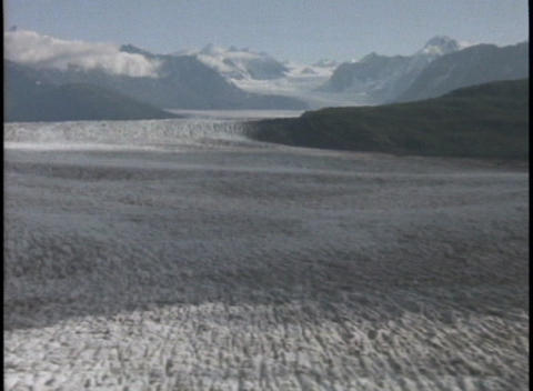 An ice and snow field leads to mountains in the distance Stock Video Footage