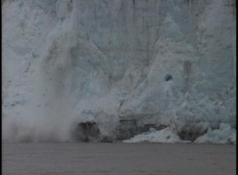 Ice breaks off of a glacier and falls into the ocean Footage