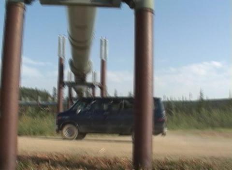 A van passes underneath the Alaskan pipeline Stock Video Footage