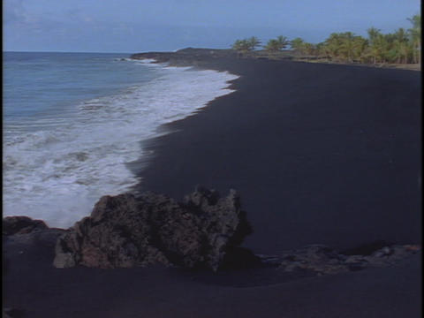 Waves roll onto a black sand beach Stock Video Footage