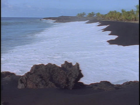 Waves roll onto a black sand beach Footage