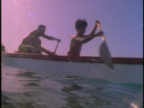 men and a boy paddle an outrigger through ocean waters Stock Video Footage