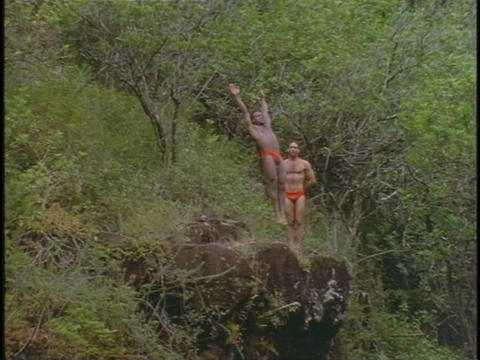 A man does a somersault dive off a high cliff Stock Video Footage