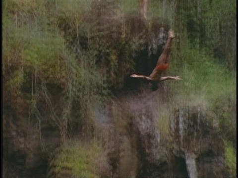 A man does a somersault dive off a high cliff Footage